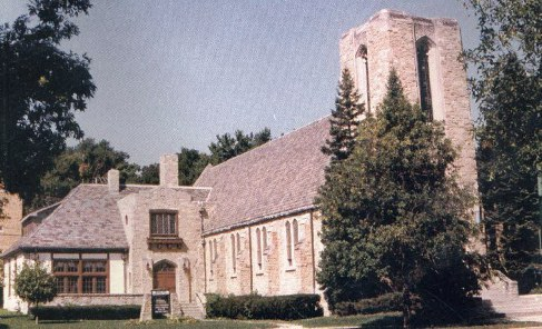 Color photo of the front of MPPC with large pine tree in front of bell tower