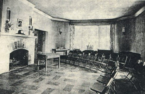Interior of Fireside Room showing Fireplace on left, folding chairs in a circle facing fireplace, windows to the rear of photo, floor patterend tile. circa 1945 black and white photo