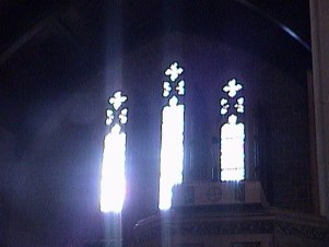 Color photo of light streaming in three windows at back of sanctuary 2005