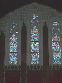 Color photo of light streaming in three windows at back of sanctuary 2005... Widnows dedicated to John Montgomery and the Trautmean family.